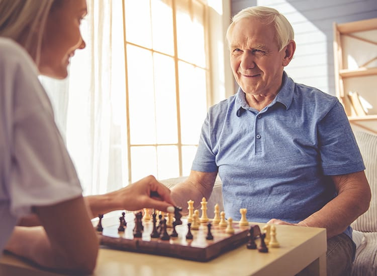Happy FountainBrook Assisted Living & Memory Support resident enjoying a game of chess